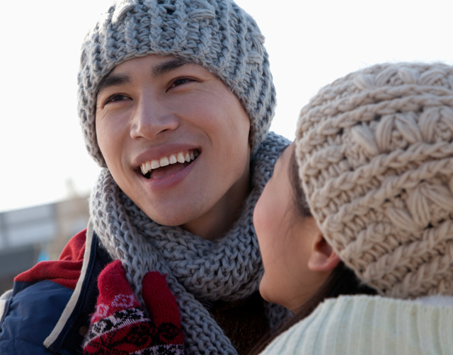 Close-up of a young Asian couple wearing knitted hats and scarves, hugging and laughing.
