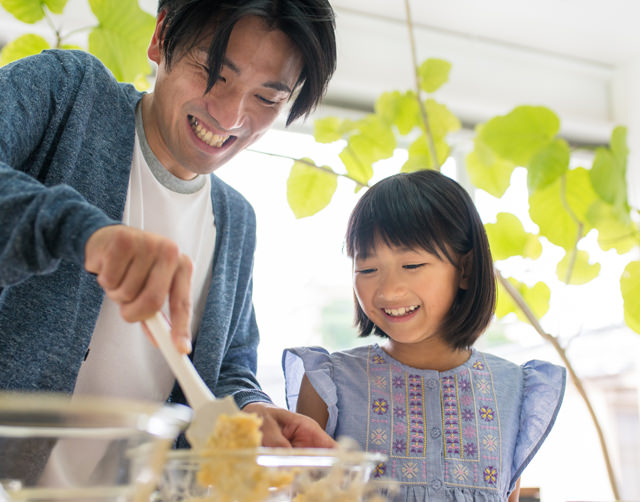 Asian father and daughter in a sun-filled kitchen, stirring a bowl of batter together.