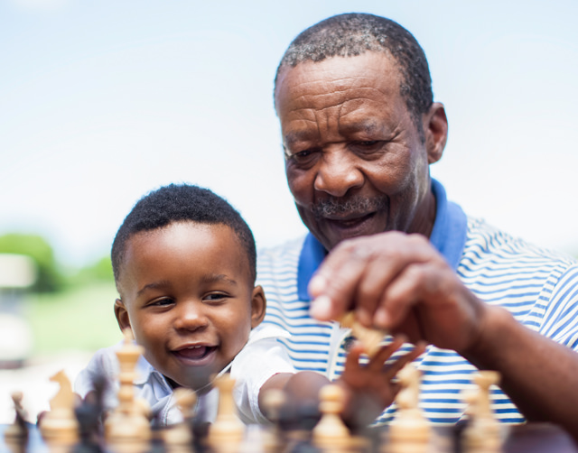 Black grandfather and grandson, sitting in front of a chess board, reaching for the chess pieces in an outdoor setting.