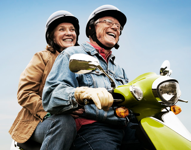 Couple in their 60's wearing helmets and riding a scooter together.