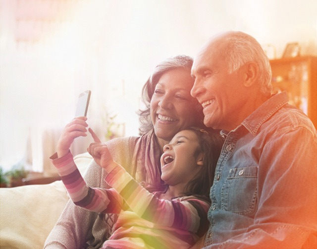 Senior couple wearing straw sun hats and gardening gloves, dancing in the garden and smiling at each other.