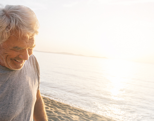 Close up of a senior man looking down at the sand and smiling to himself as he walks along the beach at sunset.