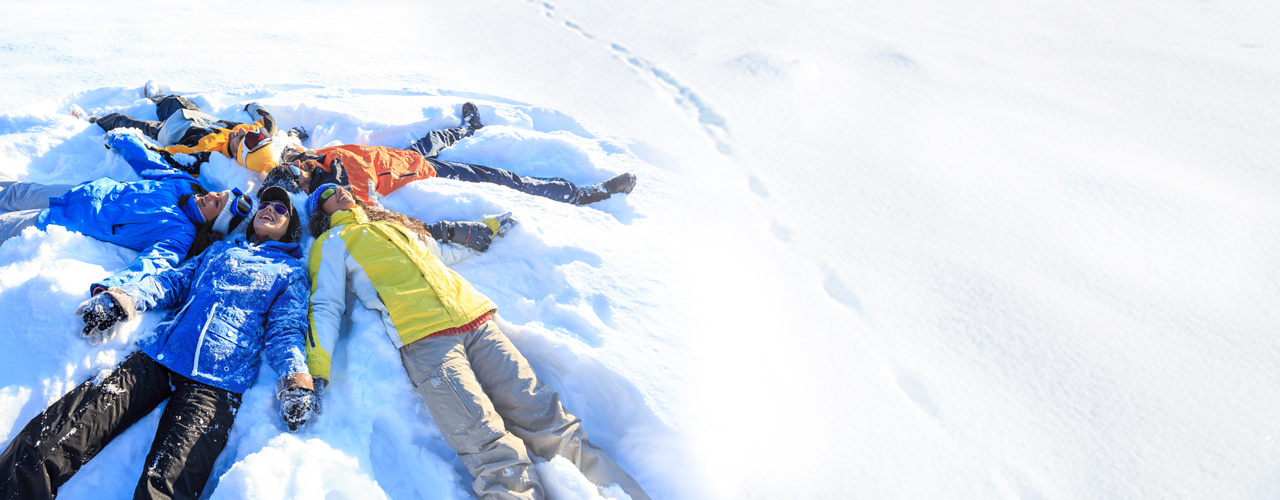 Group of five tween-aged kids wearing bright snow gear, all lying in a snow bank with heads touching, making snow angels together.