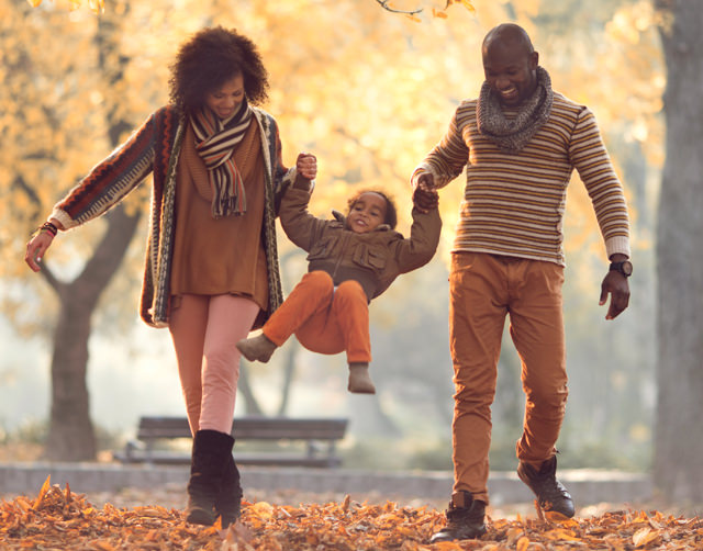 Young black couple walking down a leafy street wearing casual fall clothes, both holding hands with their young child and swinging her between them as they walk.