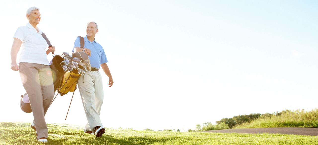 Senior couple dressed in golf attire, walking a golf course on a sunny day, each with their bag of clubs swung over their shoulders.