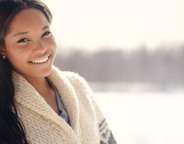 Close up of young Indigenous woman wearing a cozy sweater and smiling at the camera.