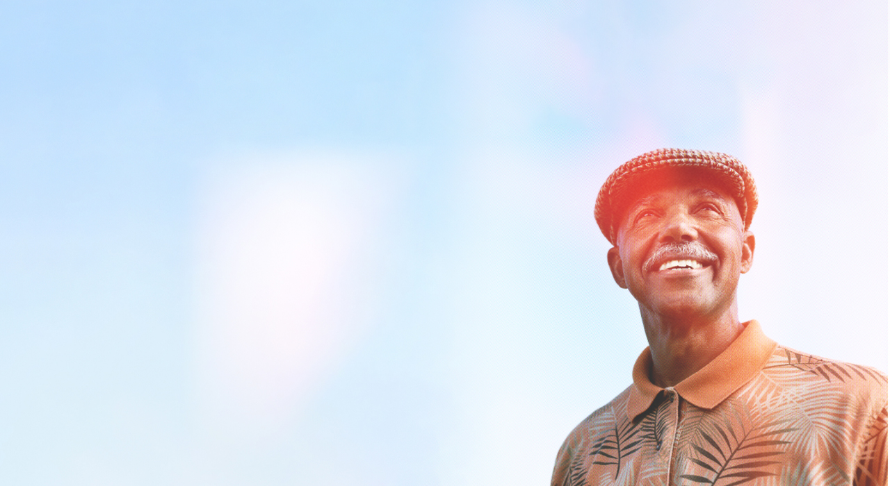 Older Asian couple, strolling along a white-sandy, tropical beach with arms around each other.